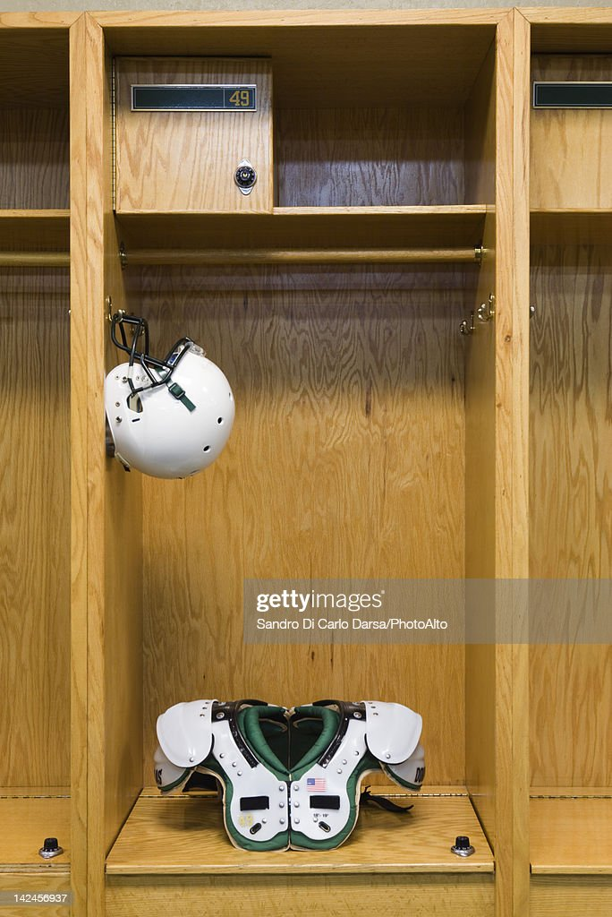 Football helmet and shoulder pads in locker room : Stock Photo