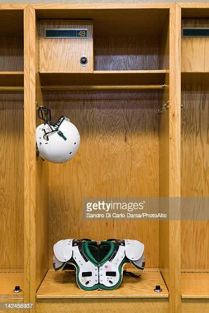 Football helmet and shoulder pads in locker room