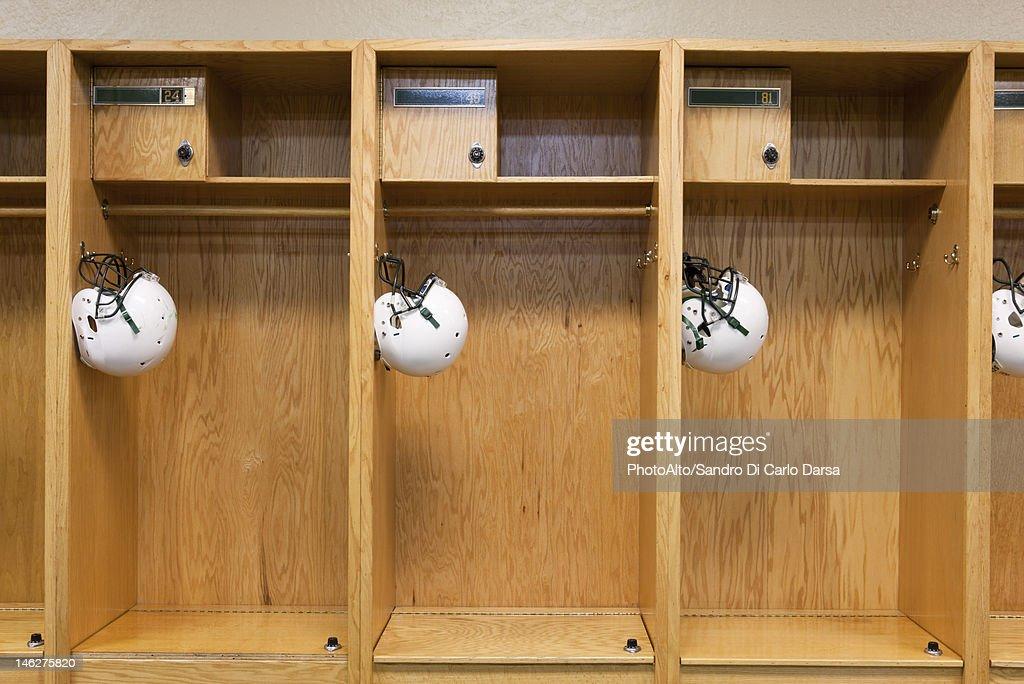 Football helmets hanging in locker room