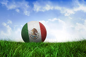 Football in mexico colours on field of grass under blue sky