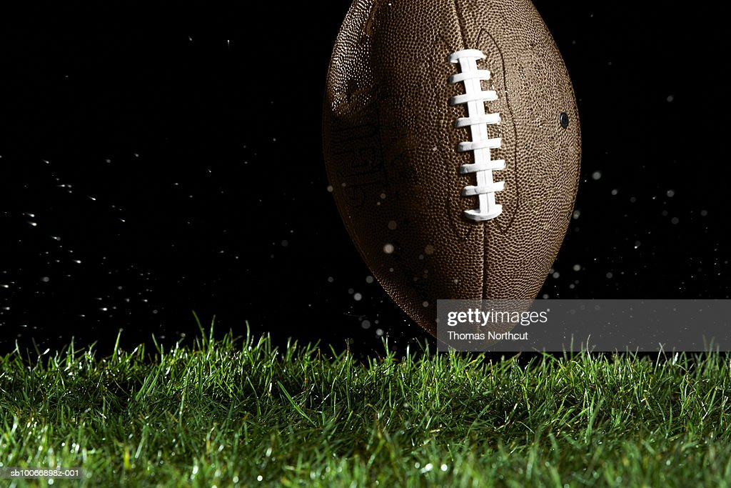 Football in motion over grass : Stock Photo