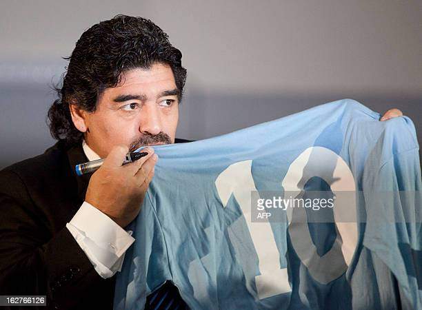 Football legend Argentinian Diego Maradona kisses a SSC Napoli number 10 jersey during a press conference on February 26 2013 in Naples Maradona who...