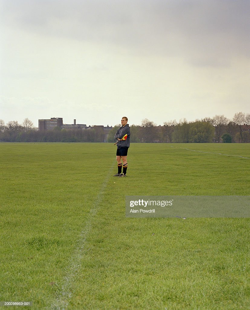 Football linesman holding flag in field : Stock Photo