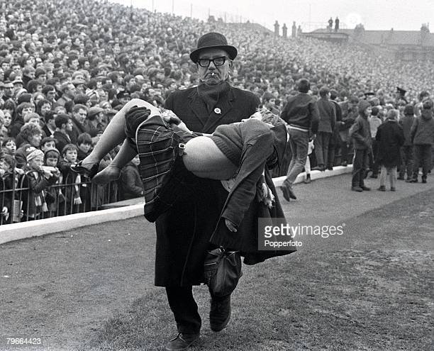 Football London England 17th January 1970 A steward carries a young girl for treatment after she was injured by fans fighting on the terraces prior...