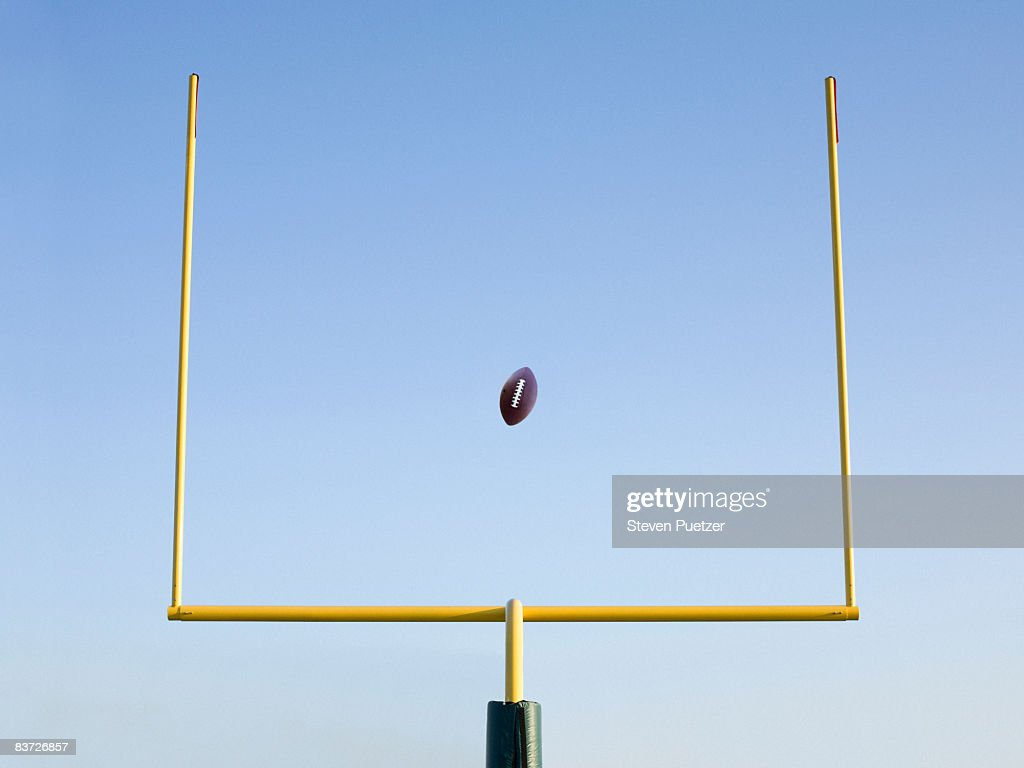 Football mid-air flying through goal post