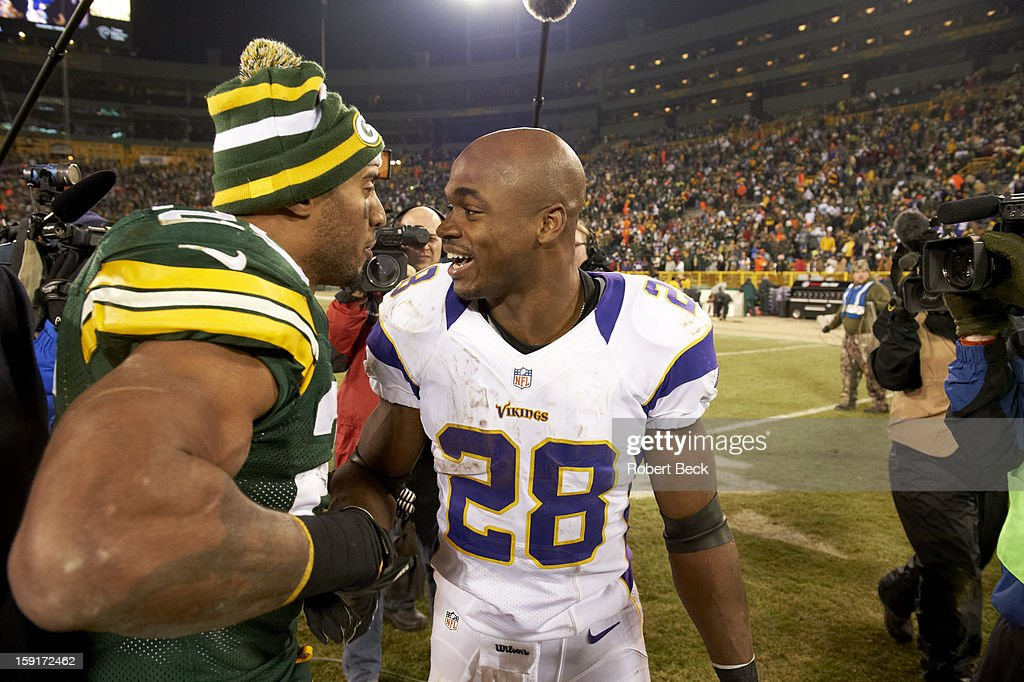 Minnesota Vikings Adrian Peterson (28) on field with Green Bay Packers Ryan Grant (25) after game at Lambeau Field. Robert Beck F137 )