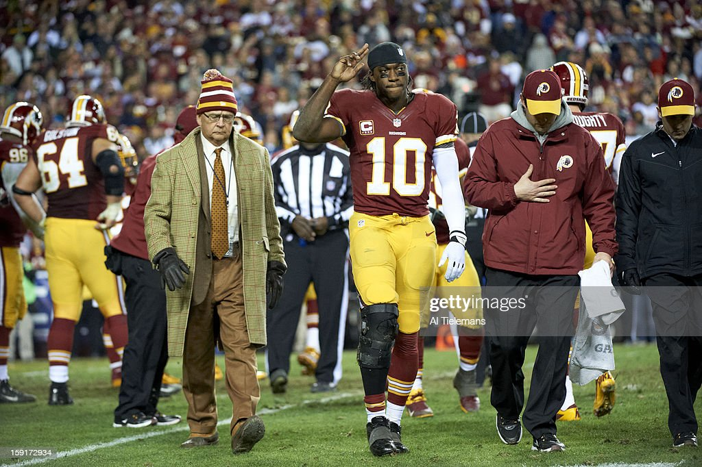 Washington Redskins QB Robert Griffin III (10) walking off the field with Dr. James Andrews (L) after re-injuring his knee during game vs Seattle Seahawks at FedEx Field. Al Tielemans F495 )