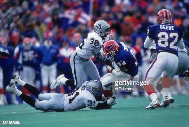 NFL Playoffs Los Angeles Raiders Rickey Dixon and Nick Bell in action defense vs Buffalo Bills Thurman Thomas at Rich Stadium Orchard Park NY CREDIT...