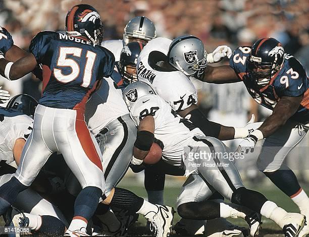 Football Oakland Raiders Napoleon Kaufman in action rushing vs Denver Broncos John Mobley and Trevor Pryce Denver CO