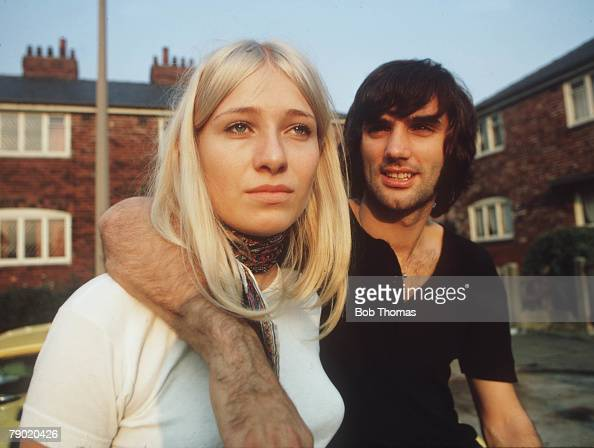 Football October Manchester United star George Best puts his arm around his fiancee Eva as they sit on the bonnet of his yellow Sports car outside...