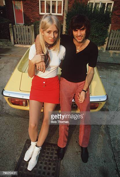 Football October Manchester United star George Best puts his arm around his fiancee Eva as they sit on the bonnet of his yellow Sports car to show...