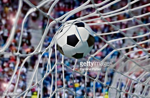 Football, or soccer ball in the back of a net