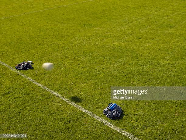 Football passing through make-shift goal made with jackets, on pitch