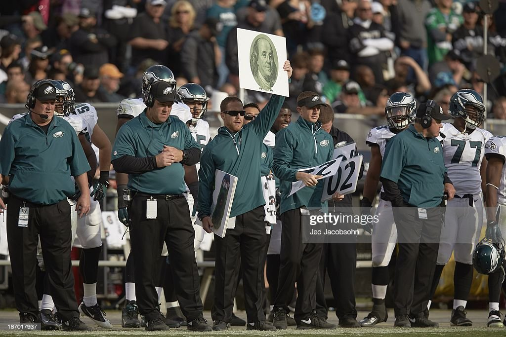 Philadelphia Eagles coach holding up card of Benjamin Franklin on sidelines during game vs Oakland Raiders at O.co Coliseum. Jed Jacobsohn F482 )