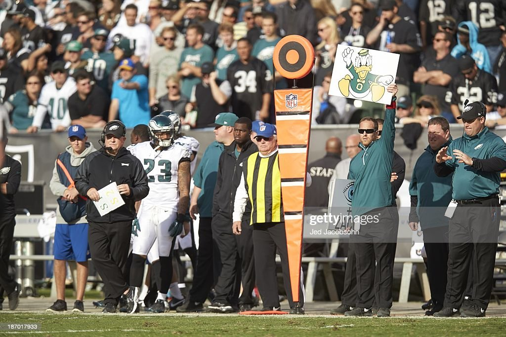Philadelphia Eagles coach holding up card of Donald Duck on sidelines during game vs Oakland Raiders at O.co Coliseum. Jed Jacobsohn F414 )