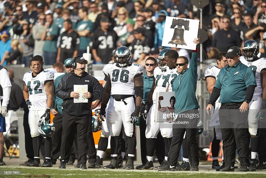 Philadelphia Eagles coach holding up card of Liberty Bell on sidelines during game vs Oakland Raiders at O.co Coliseum. Jed Jacobsohn F330 )