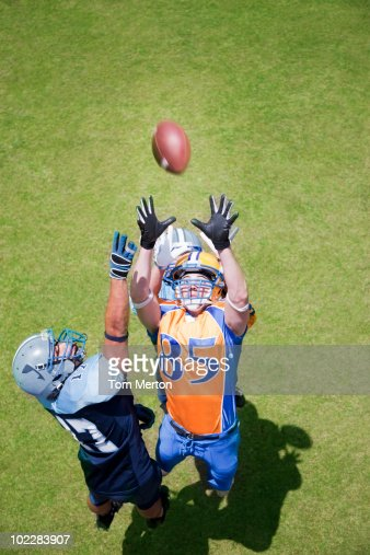 Football player catching football : Stock Photo