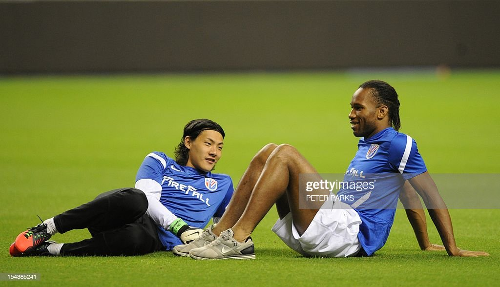 Football player Didier Drogba (R) chats to Shanghai Shenhua goalkeeper Dong Guangxiang (L) before a training session at Hongkou stadium in Shanghai on October 19, 2012. Drogba has injured his right ankle so he will not play the next match for his Chinese club after returning from international duty and into a row that has seen his teammates reportedly refusing to practise over unpaid wages. AFP PHOTO/Peter PARKS