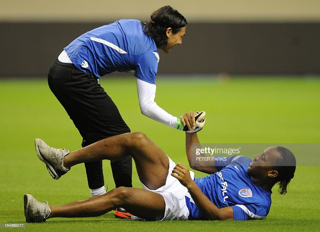 Football player Didier Drogba (R) is helped up by Shanghai Shenhua goalkeeper Dong Guangxiang (L) before a training session at Hongkou stadium in Shanghai on October 19, 2012. Drogba has injured his right ankle so he will not play the next match for his Chinese club after returning from international duty and into a row that has seen his teammates reportedly refusing to practise over unpaid wages. AFP PHOTO/Peter PARKS