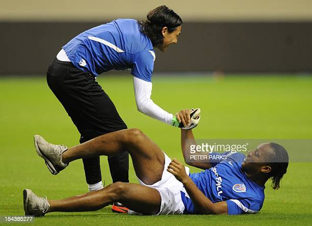 Football player Didier Drogba is helped up by Shanghai Shenhua goalkeeper Dong Guangxiang before a training session at Hongkou stadium in Shanghai on...