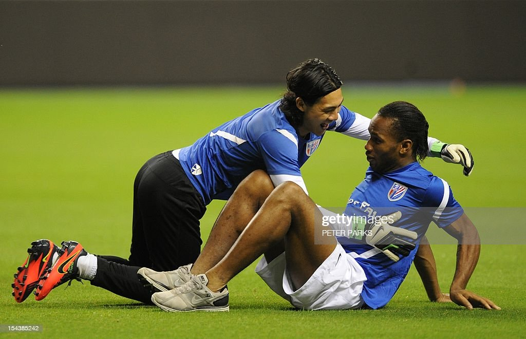 Football player Didier Drogba (R) is jumped on by Shanghai Shenhua goalkeeper Dong Guangxiang (L) before a training session at Hongkou stadium in Shanghai on October 19, 2012. Drogba has injured his right ankle so he will not play the next match for his Chinese club after returning from international duty and into a row that has seen his teammates reportedly refusing to practise over unpaid wages. AFP PHOTO/Peter PARKS