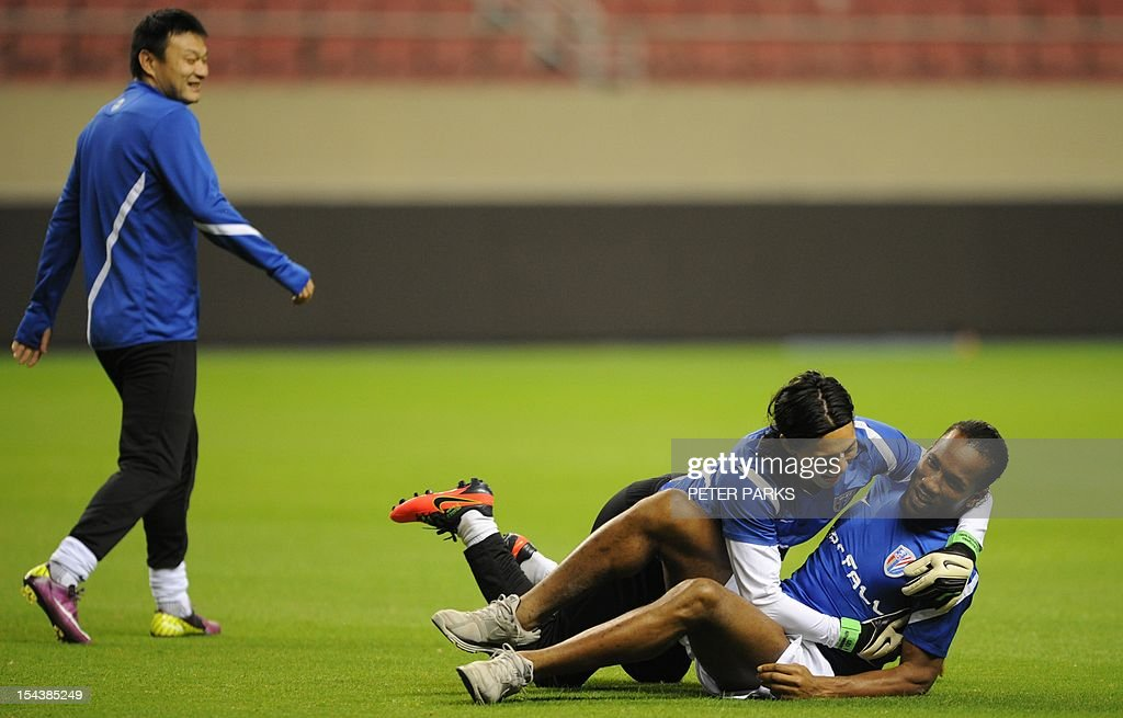 Football player Didier Drogba (R) is jumped on by Shanghai Shenhua goalkeeper Dong Guangxiang (C) as midfielder Jiang Kun (L) looks on before a training session at Hongkou stadium in Shanghai on October 19, 2012. Drogba has injured his right ankle so he will not play the next match for his Chinese club after returning from international duty and into a row that has seen his teammates reportedly refusing to practise over unpaid wages. AFP PHOTO/Peter PARKS