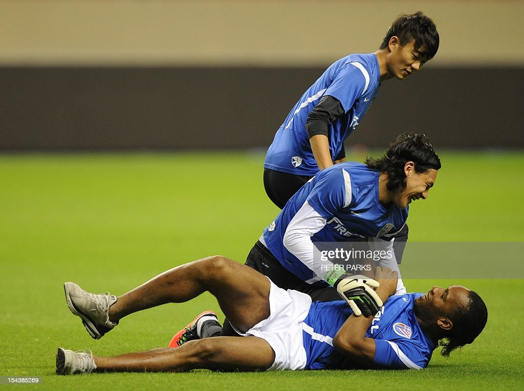 Football player Didier Drogba (bottom) is jumped on by Shanghai Shenhua goalkeeper Dong Guangxiang (C) and defender Xiong Fei (top) before a training session at Hongkou stadium in Shanghai on October 19, 2012. Drogba has injured his right ankle so he will not play the next match for his Chinese club after returning from international duty and into a row that has seen his teammates reportedly refusing to practise over unpaid wages. AFP PHOTO/Peter PARKS