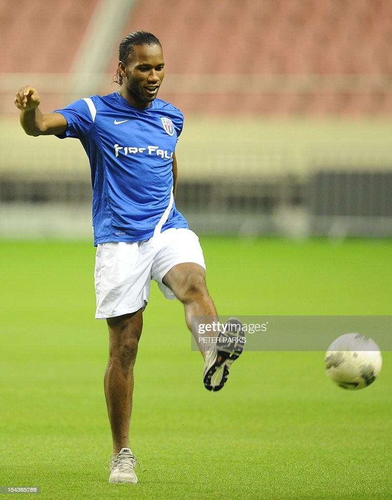 Football player Didier Drogba kicks a ball with his left foot before a Shanghai Shenhua training session at Hongkou stadium in Shanghai on October 19, 2012. Drogba has injured his right ankle so he will not play the next match for his Chinese club after returning from international duty and into a row that has seen his teammates reportedly refusing to practise over unpaid wages. AFP PHOTO/Peter PARKS