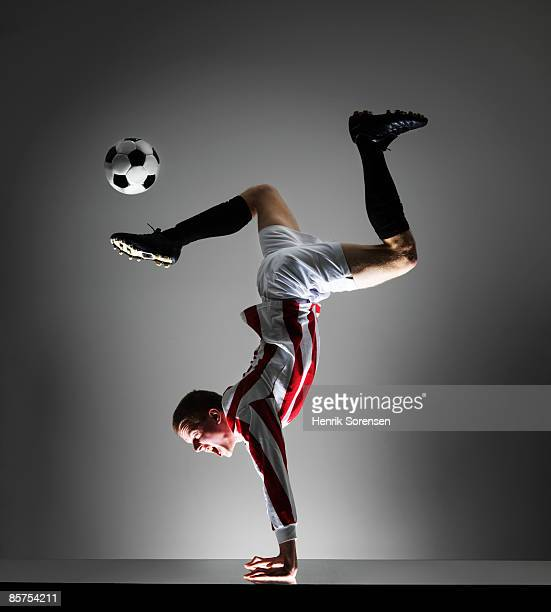 Football player doing a handstand while kicking