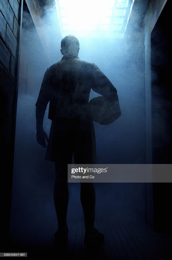 Football player entering steam room, rear view : Stock Photo