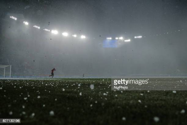 A football player hides from the hail before the start of the Russian Football League match between FC Zenit St Petersburg and FC Spartak Moscow at...
