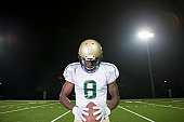 Football player holding ball, head down in concentration