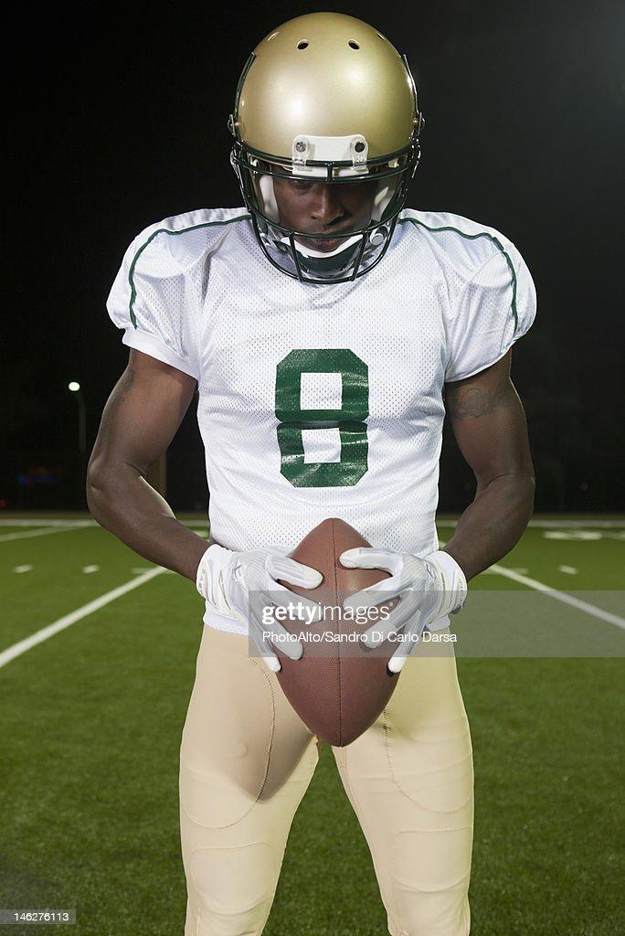 Football player holding ball, portrait