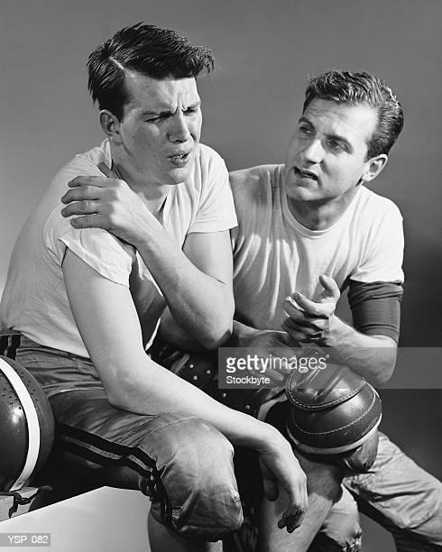 Giocatore di calcio che tiene dolorante spalle; trainer seduto accanto a lui