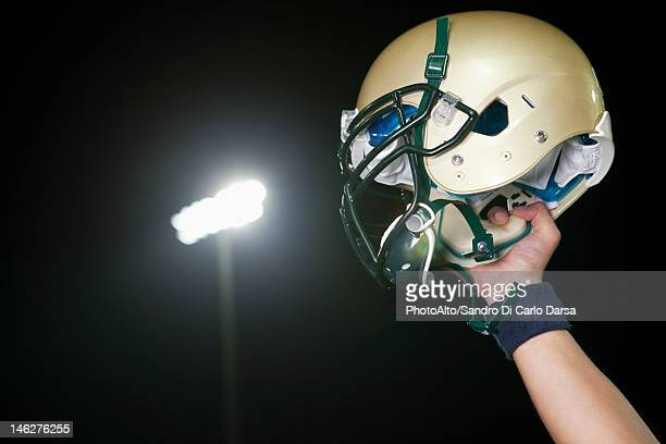 Football player holding up helmet in victory, cropped