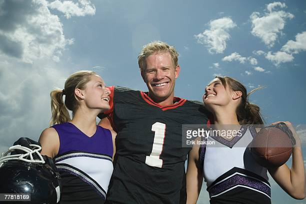 Football player hugging cheerleaders