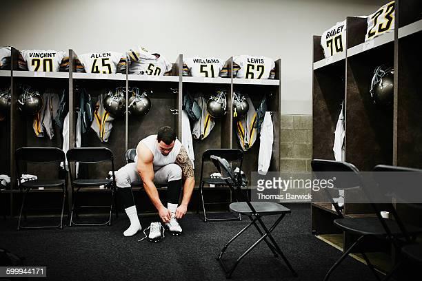 Football player in locker room preparing for game
