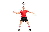 Full length portrait of a young male football player juggling a ball on his head isolated on white background