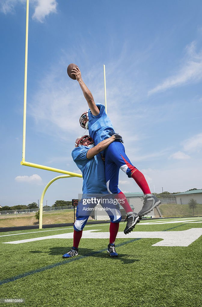 Football Player Jumping to Catch Ball for Touchdown in Endzone
