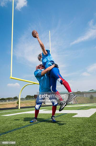 Joueur de Football de sauter pour reprendre contact au ballon pour Endzone