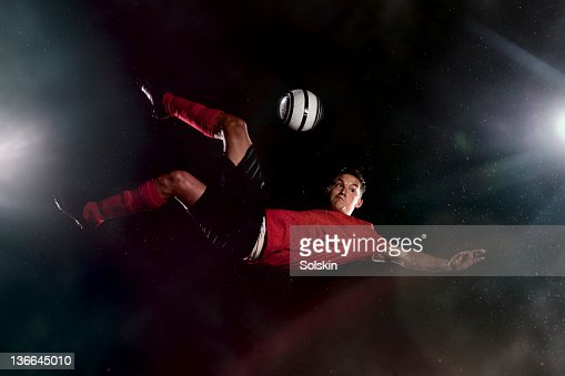 football player kicking ball in mid air : Stock Photo