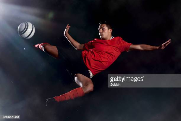 football player kicking ball in mid air