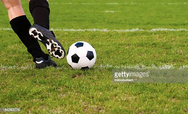 Football player kicks a soccer ball on a field