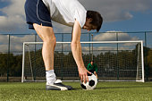 Football player lining up ball in front of goal post