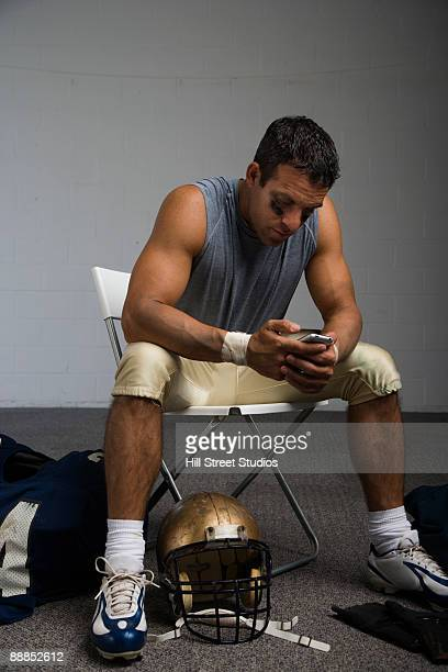 Football player looking at cell phone in locker room