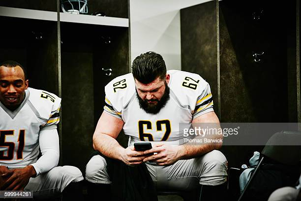 Football player looking at smartphone before game