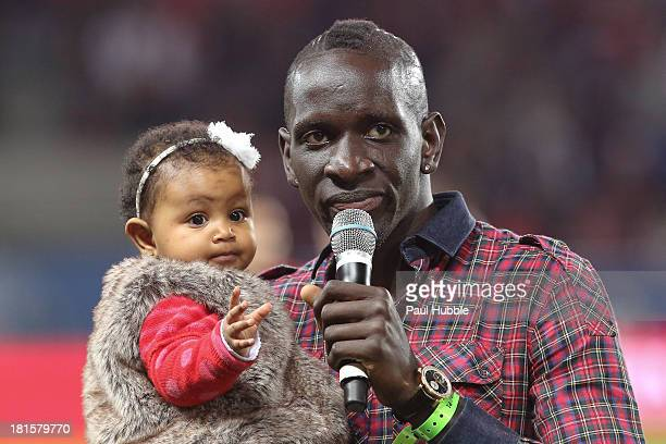Football player Mamadou Sakho of Liverpool delivers a speech to the fans of his former Paris Saint Germain as he carries his young daughter during...