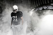 Football player in a black uniform, leaving a smoky tunnel, ready to get on the field