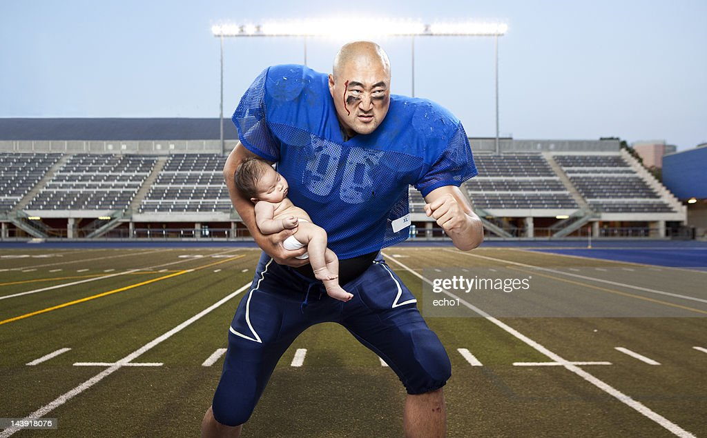 football player protecting baby