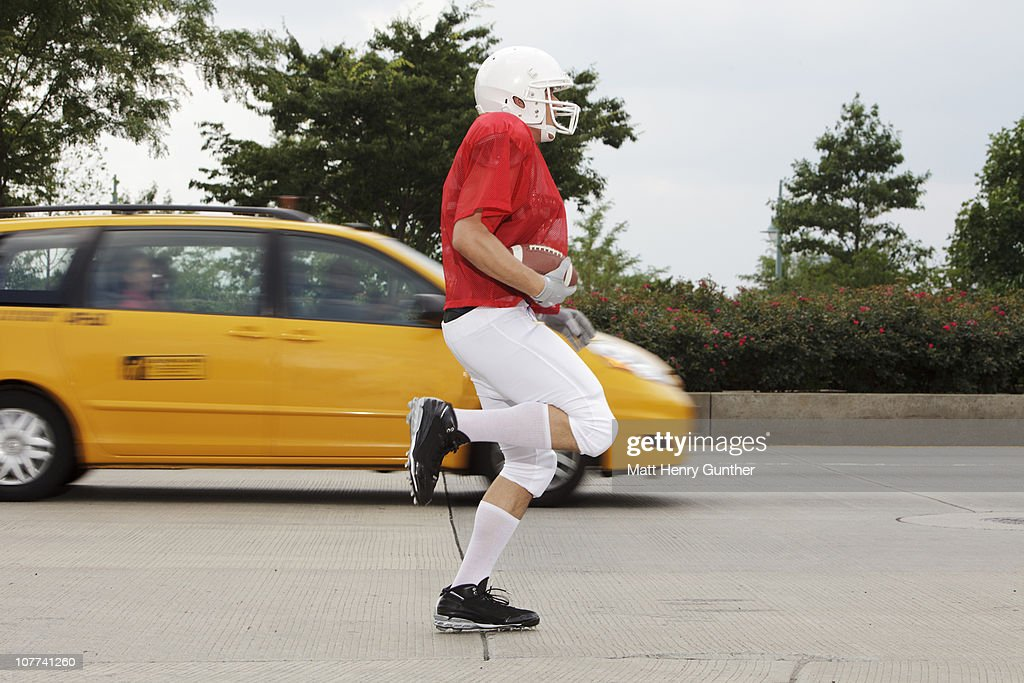 Football player running in the streets of New York : Stock Photo